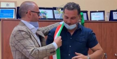 Antonio De Caprio mentre consegna la fascia tricolore al vicesindaco Alberto Bottone