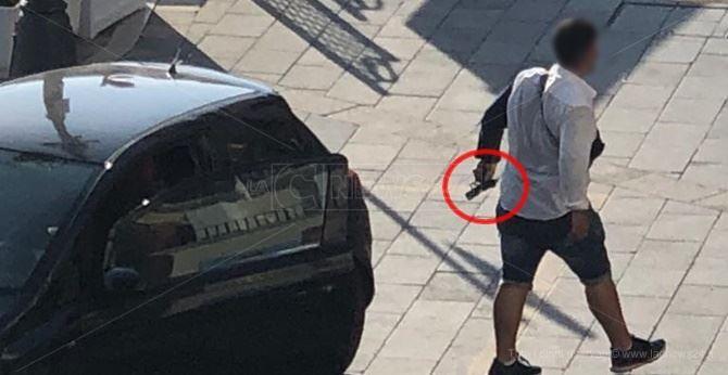 Uno degli aggressori con la pistola in mano