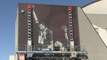 Jorit al lavoro sulla facciata del Palazzetto dello Sport di Rende