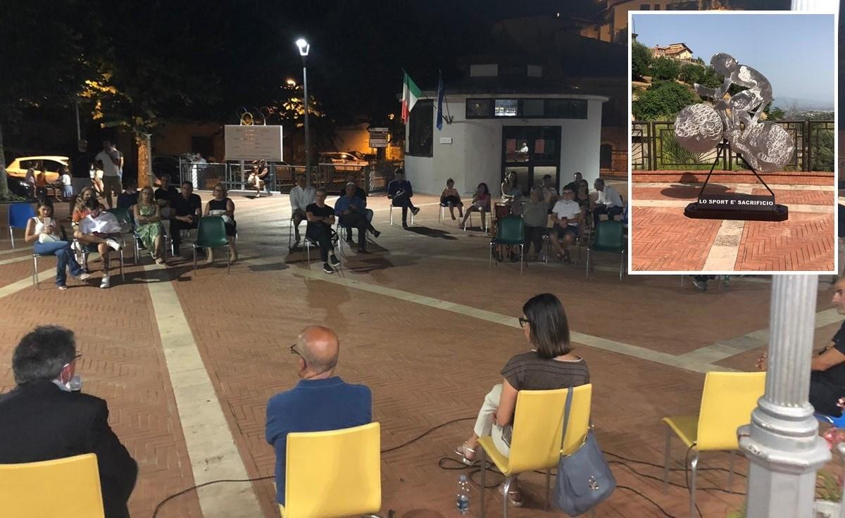 La cerimonia in piazza e, nel riquadro, la scultura