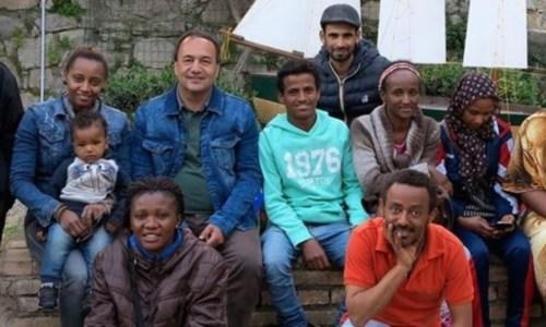 Mimmo Lucano insieme a un gruppo di migranti