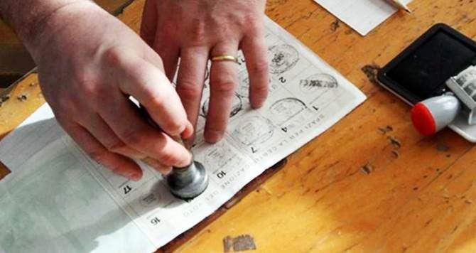 Una scheda elettorale timbrata da uno scrutatore