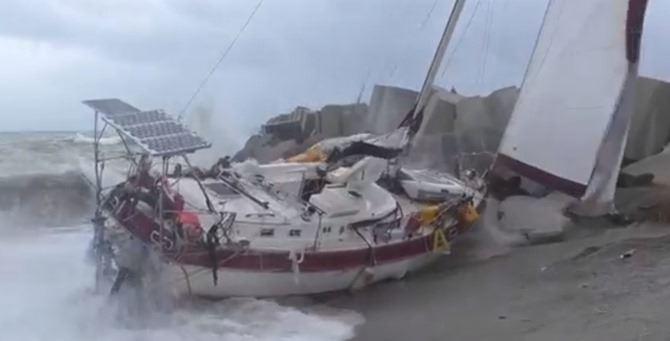 La barca finita sulla spiaggia dopo l'impatto con il molo