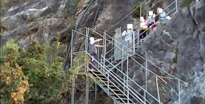Alcuni turisti sulla scala che dà accesso alla spiaggia della Grotta del Prete