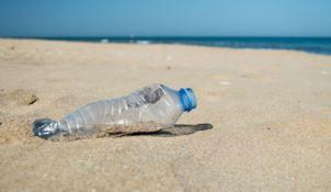 Una bottiglia abbandonata in spiaggia