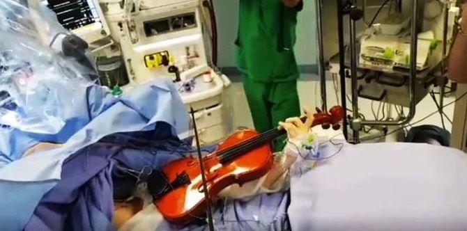 Suona il violino durante l'operazione (foto Ansa)