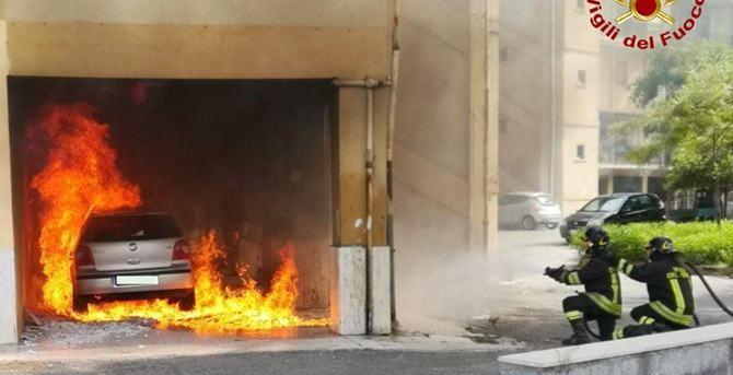 L'auto in fiamme e i vigili del fuoco in azione
