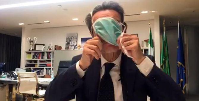 Attilio Fontana mentre indossa maldestramente la mascherina